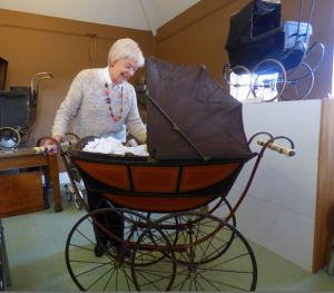 Julie Marshall with the oldest pram in the exhibition