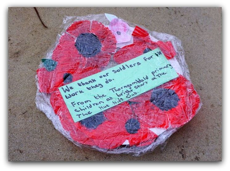 One of the Paper Poppy Wreaths wrapped to protect it from the rain